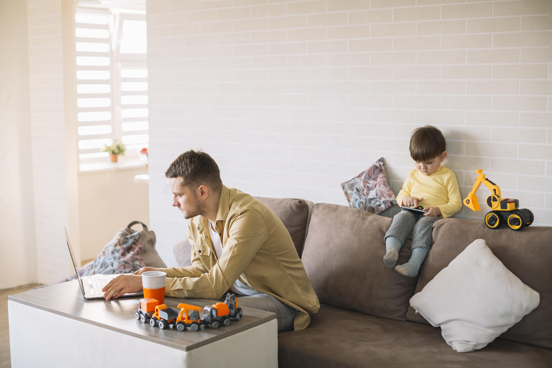 Hombre trabajando en casa en un salon con su hijo